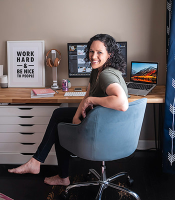 Becky sitting in chair in office turned away from desk looking at camera