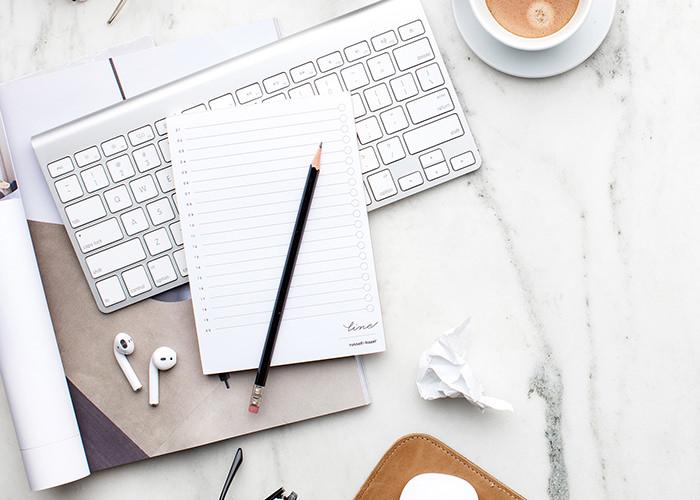 flatlay of computer keyboard and notepad and pencil