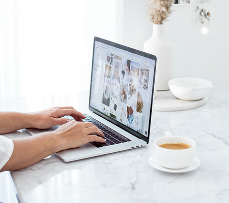 woman sitting at a marble desk with a coffee looking at images on a laptop