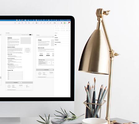 imac on desk with website design mockups on screen